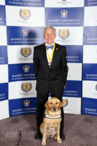 Don Mckenzie and his guid dog, a yellow Labrador named Holly, stand in front of a Massey university sign. Don is wearing a medal around his neck. Holly is sitting bolt upright as if she expects a medal of her own.