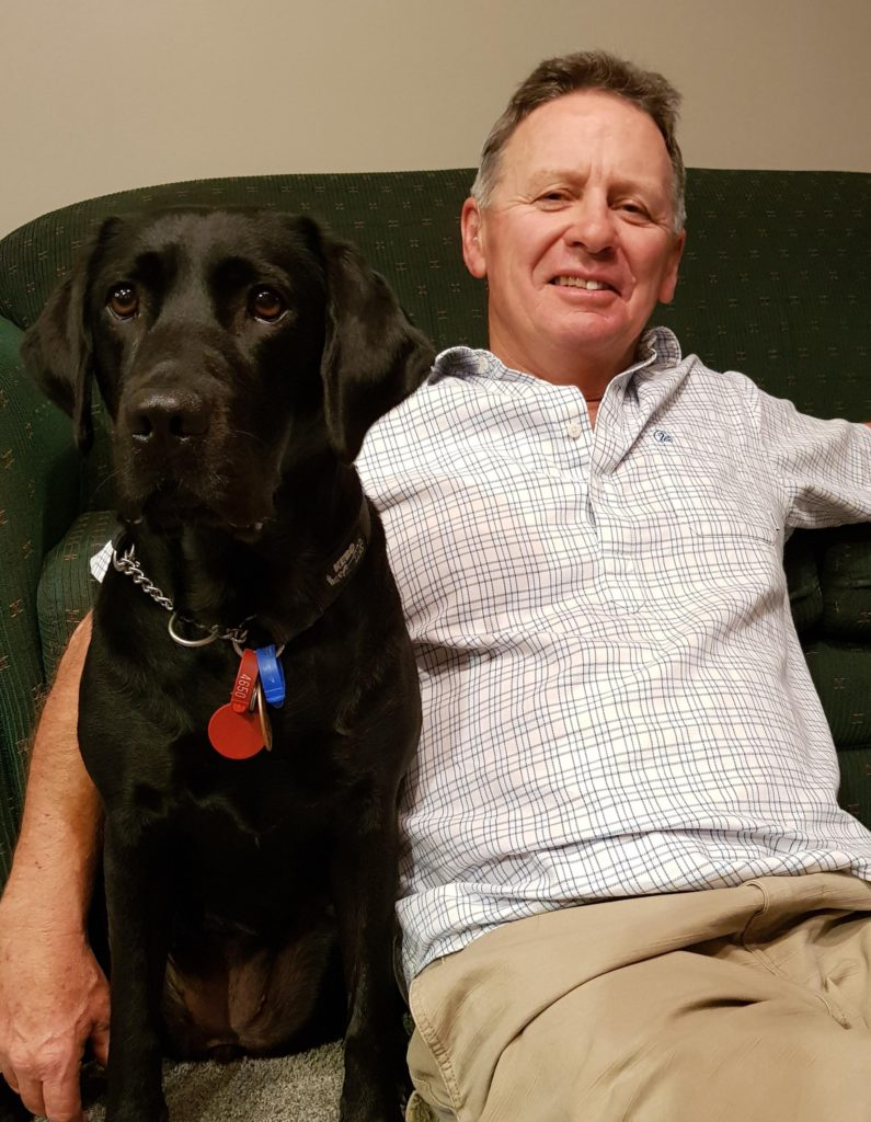 David Wilson sits on a couch with his guide dog, a black Labrador named Cayla