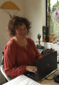 Amanda Stevens sitting at a desk working on her laptop