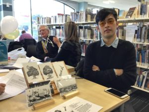 Deafblind artist with his sketches on postcards